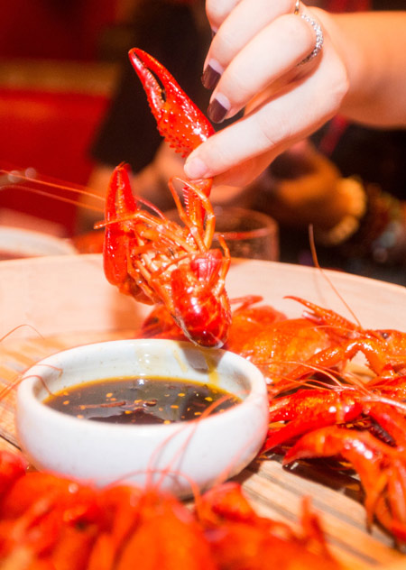 a diner enjoys a popular dish of crayfish with spicy sauce ...