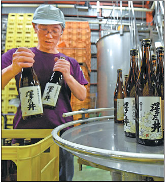 An Employee Of The Ozawa Shuzo Brewery Puts Bottles Of