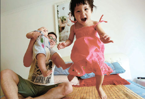 a girl shares a fun moment with her father and her brother ...