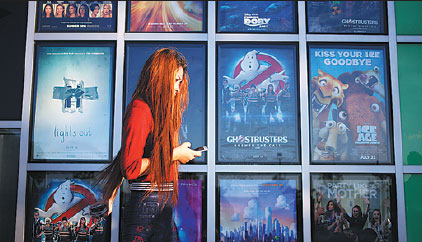 A Woman Walks Past A Display Of Movie Posters Outside Of