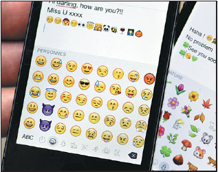 Emoji Characters On The Screens Of Two Mobile Phones The