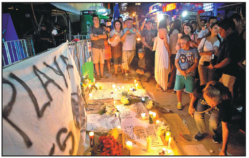 Local Residents Gather To Place Candles And Banners In A