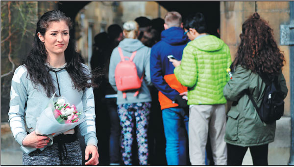 A Student Carries Flowers As Others Queue To Sign A Book