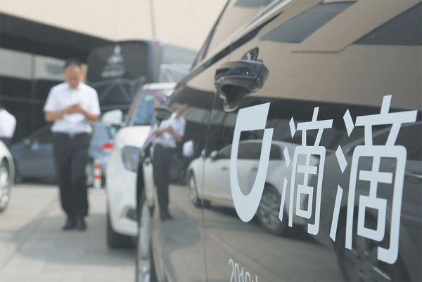 a pedestrian passes by a chauffeured car of didi chuxing ...