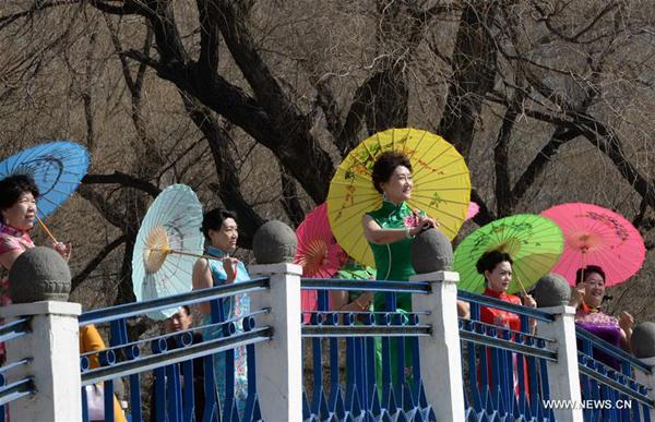 women present cheongsam to mark coming international women