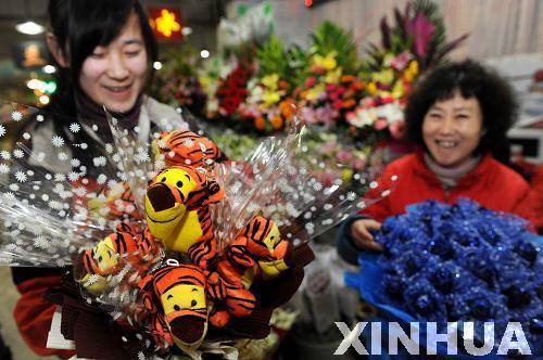 2月10日,青岛南山花卉市场一位花店员工(右)在摆放鲜花.
