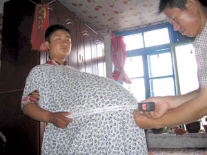 ... has her phenomenally big belly measured by her husband on June 11, 2006.