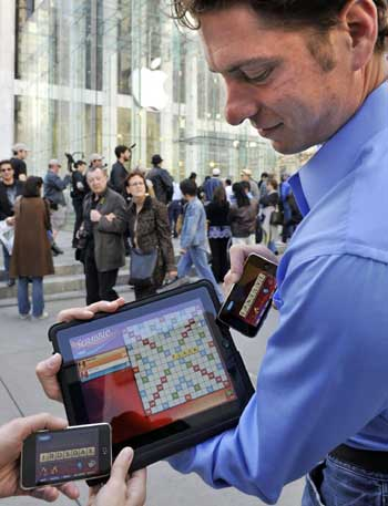 ... of EA Mobile demonstrates the 'Scrabble' application for the newly released iPad, using an iPod Touch as 'tile rack,' outside the 5th Avenue Apple Store ... - 0022190dec450d2226c411