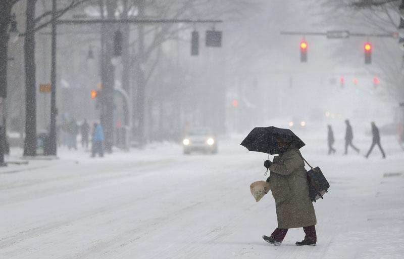 woman cross a street as snow falls in Charlotte, North Carolina