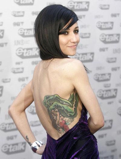 Singer lights shows off her tattoo while on the red carpet during the