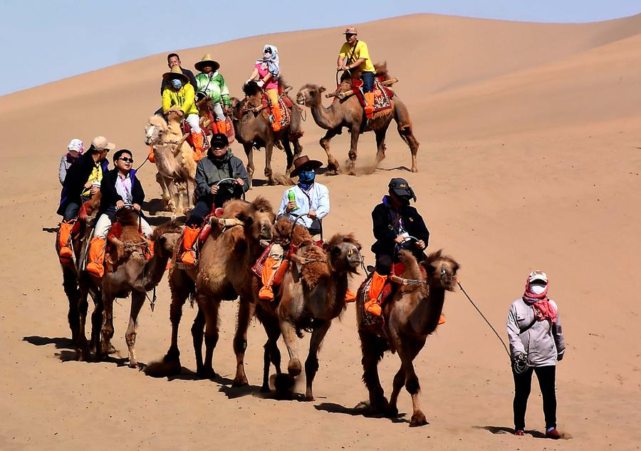 Tourists try camel riding at Mingsha Hill desert[1