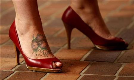A sex worker sporting a tattoo on her foot participates in a protest in ...