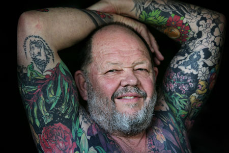 Retired teacher Geoff Ostling displays his tattooed skin at a portrait