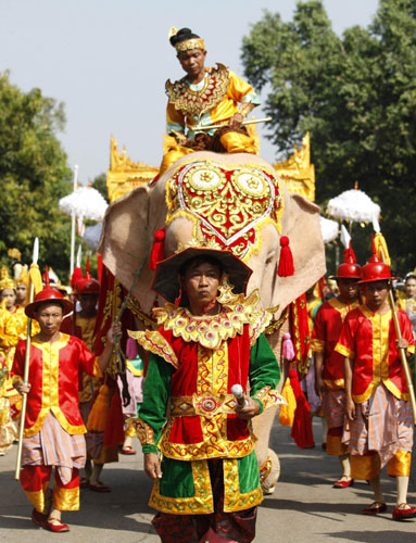 People parade with a white elephant and a vehicle carrying a sacred Buddha tooth relic from China, encircling the grounds of the Maha Pasana Cave in Yangon Nov 22, 2011.
