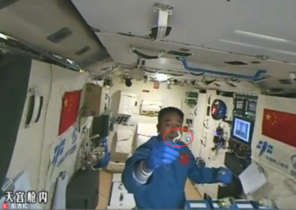 Astronaut plays with silkworms in Tiangong II